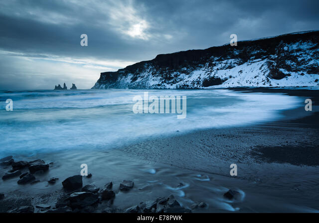 the black sand beach at Vík í Mýrdal in winter, with the Renisdrangar basalt sea stacks beyond, southern - Stock Image