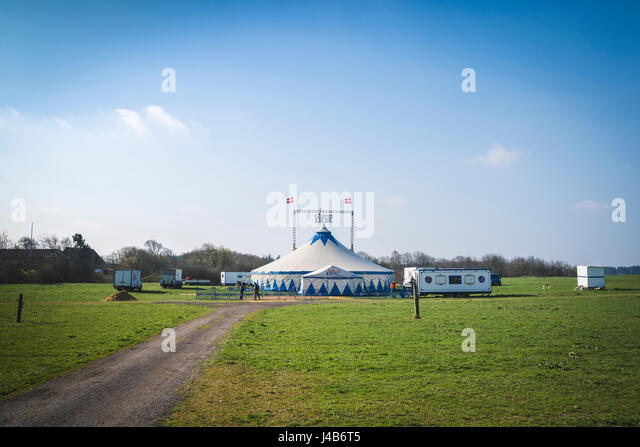 THEM, DENMARK - APRIL 9 - 2017: Circus Krone setting up a tent on a field in Them with workers creating a fence - Stock Image