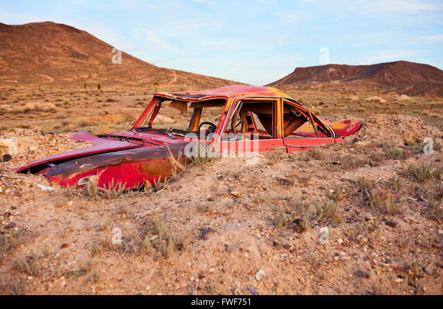 Junk car artistically buried in the desert near Goldfield, Nevada - Stock-Bilder