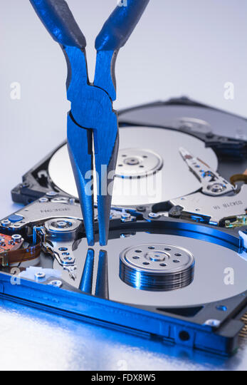 Pair of DIY pincers poised over platter of a stripped hard disk drive - visual metaphor for concept of software - Stock Image