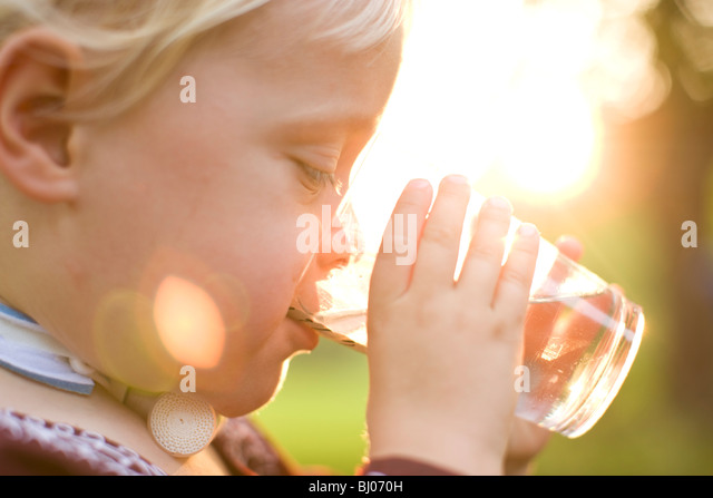 Young boy drinking a glass of water. - Stock Image
