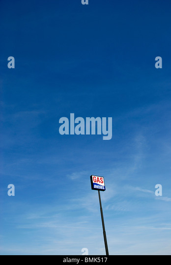 Gas station sign with the words Gas and Diesel on a long pole against blue sky. - Stock Image