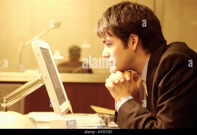 Businessman staring at computer monitor - Stock Image