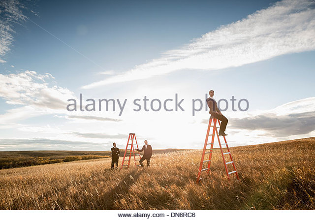 Businessmen looking at colleague sitting on ladder - Stock Image