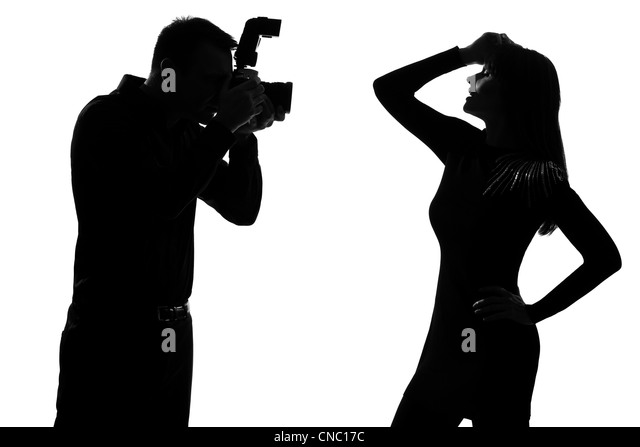 one caucasian  couple man photographer photographing and woman fashion model posing in studio silhouette isolated - Stock Image