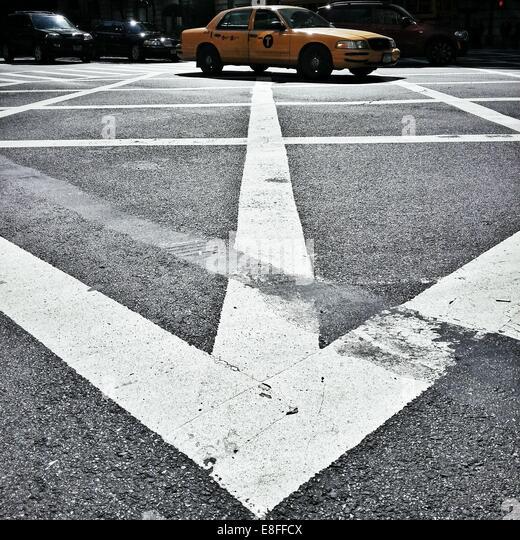 Yellow Cab driving across box junction, Manhattan, New York, America, USA - Stock Image
