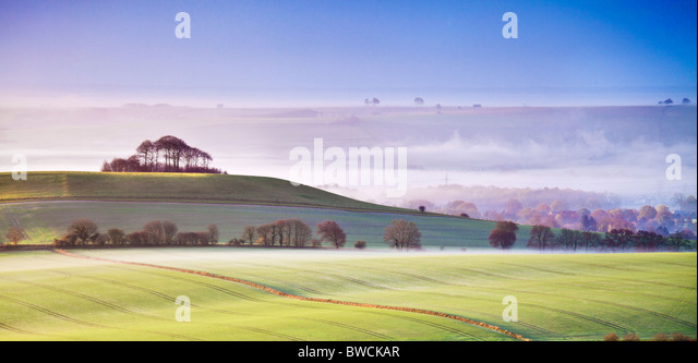 Misty autumn sunrise from Knapp Hill towards Woodborough Hill and the Vale of Pewsey in Wiltshire, England, UK - Stock Image