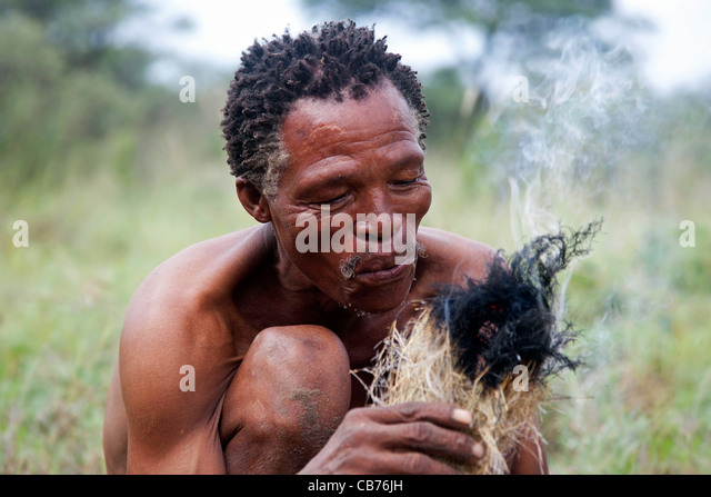 Bushman starting fire in the Kalahari desert near Ghanzi, Botswana, Africa - Stock Image