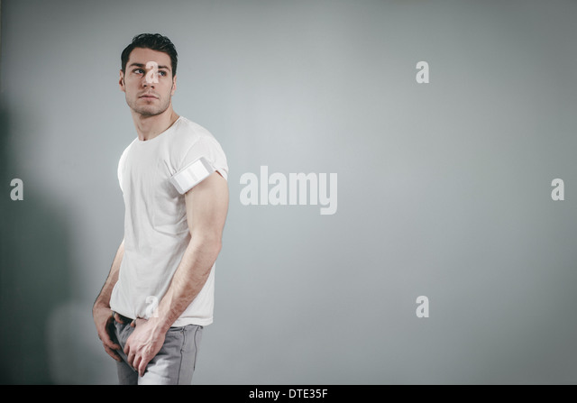 Part of series showing different ways one carries a smartphone, folded in t-shirt sleeve oldschool style. - Stock Image