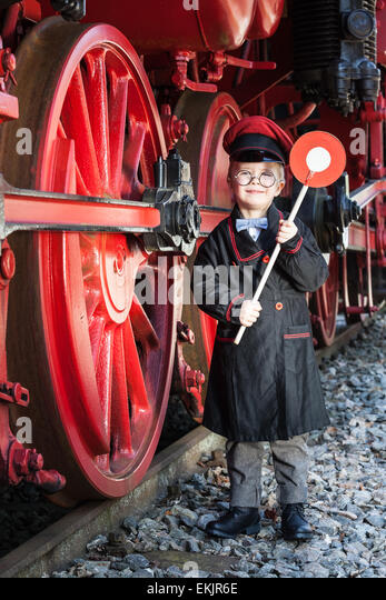 Little child boy as nostalgic railroad conductor with cap and signaling disk beside large wheels of a steam locomotive - Stock-Bilder