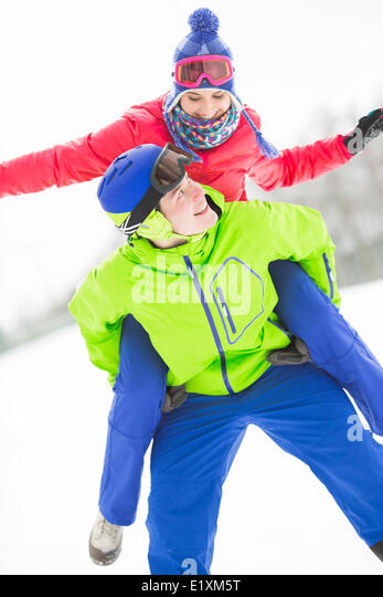 Happy young man giving piggyback ride to woman in snow - Stock Image