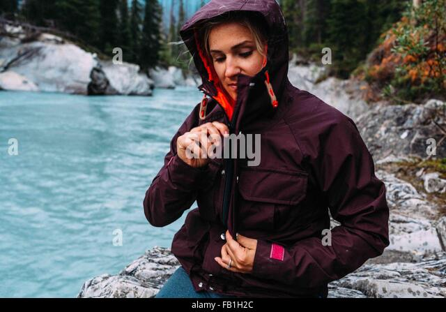 Mid adult woman by waters edge zipping up waterproof coat, Moraine lake, Banff National Park, Alberta Canada - Stock Image