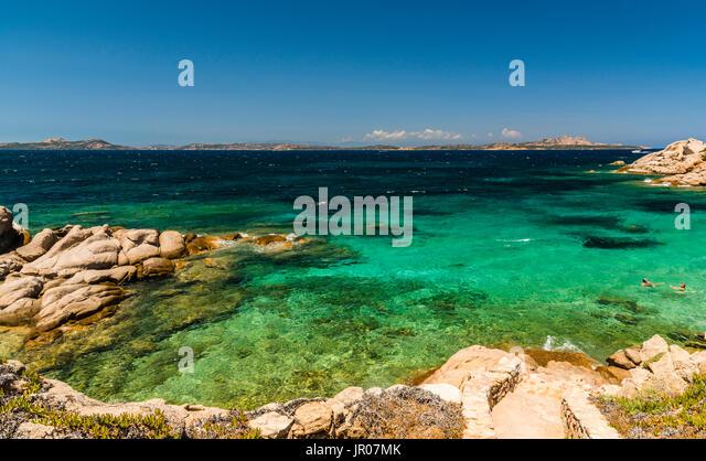 Wonderful azure seas and swimmers around Baya Sardinia, Italy - Stock Image