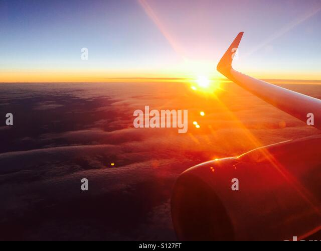 A view of the sun setting from an airplane. - Stock Image