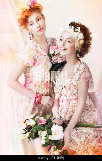 Freshness. Two Young Pretty Women in Classic Vintage Dresses with Flowers. Pin-up Style - Stock Image
