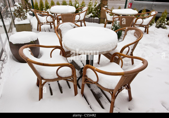 The Netherlands, Slenaken, Chairs of outdoor cafe, covered with snow. - Stock Image