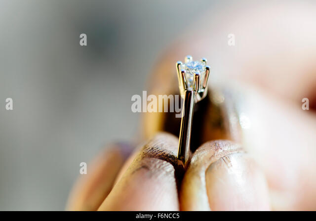Ring held by jeweler after polishing it - Stock Image