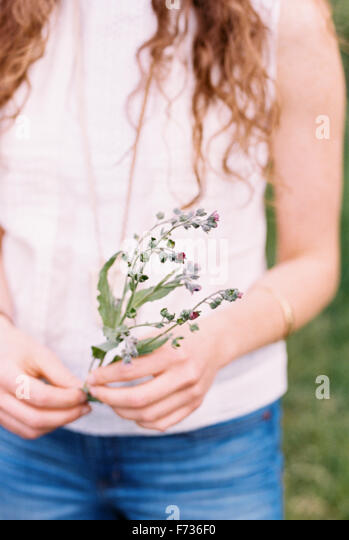 Close up of a woman holding a wild flower. - Stock Image