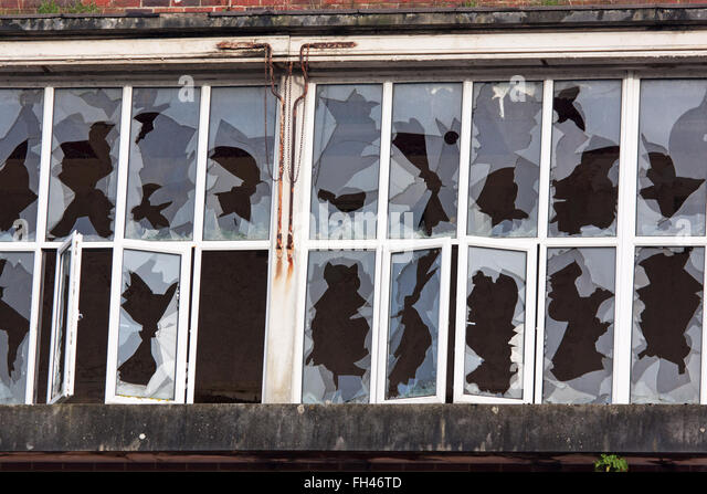 Vandalized window panes in a disused industrial building - Stock Image
