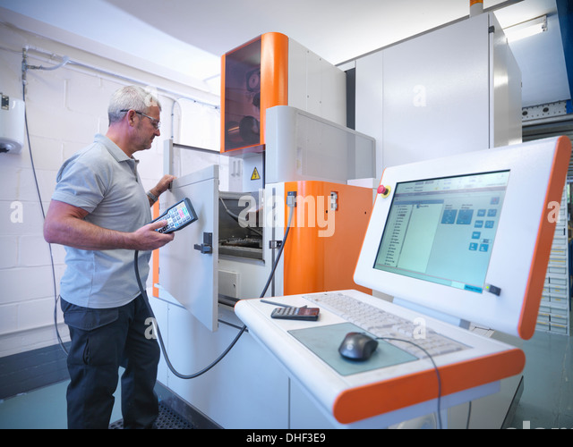 Engineer operating wire erosion machine in factory - Stock Image