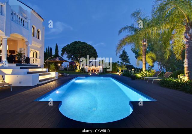 Illuminated pool outside villa - Stock Image