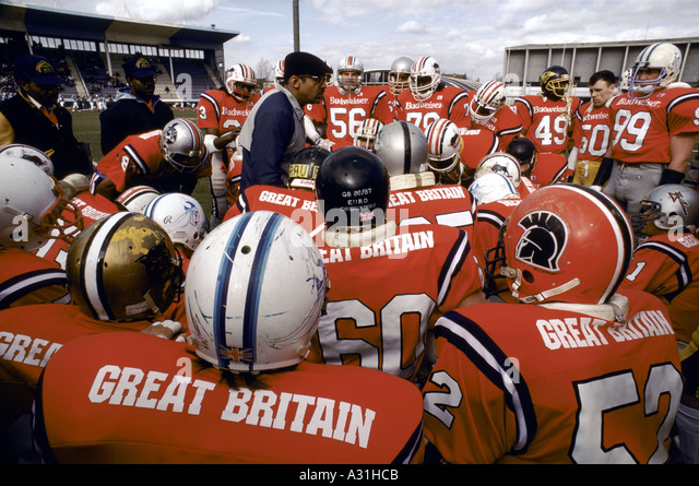 british american football team huddle around warren tate chief coach 1987 1987 - Stock Image