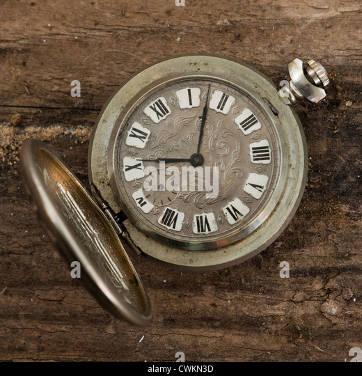 antique pocket watch on a wooden background - Stock Image