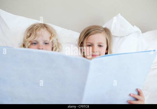 Siblings reading bedtime story - Stock Image