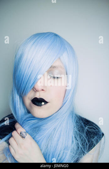 Young woman with blue hair and creative make up - Stock Image