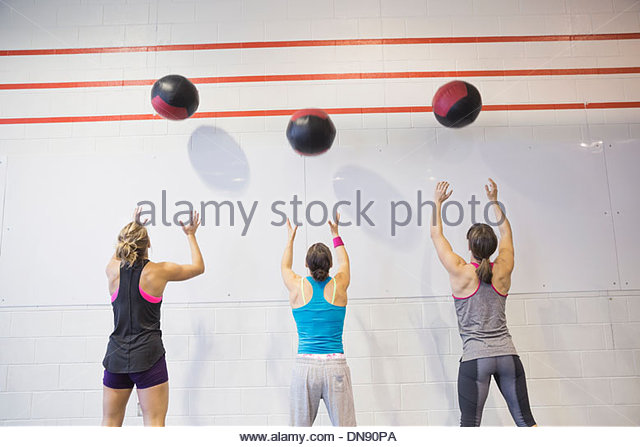 Women throwing medicine balls against wall - Stock Image