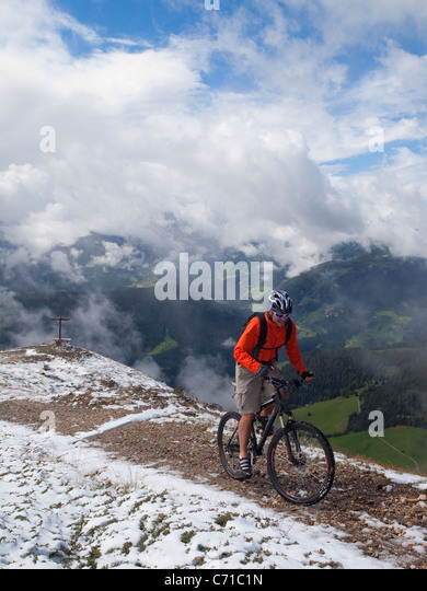 A mountain biker arrives on the summit of Kronplatz, mountains, a cross and clouds in the background. - Stock Image