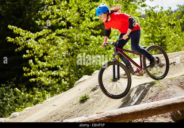 Young female bmx biker speeding down rocks in forest - Stock Image