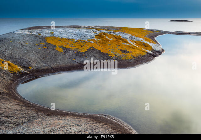 Smooth tide pool edged by mossy rock - Stock Image
