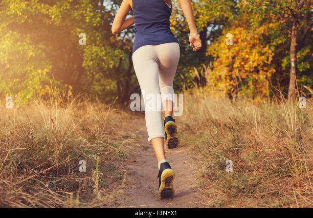 Young woman running on a rural road at sunset in autumn forest. Lifestyle sports background - Stock-Bilder