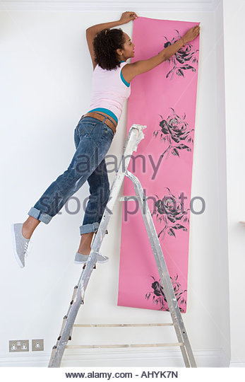 Woman hanging wallpaper from step ladder, - Stock Image