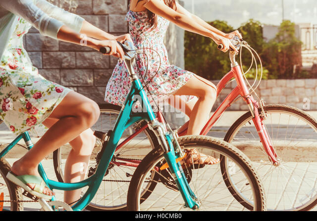 The two young girls with bicycles in park - Stock-Bilder