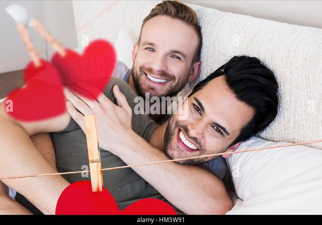 Homosexual couple embracing each other in bedroom at home - Stock-Bilder