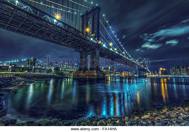 The Brooklyn Bridge and Hudson River overlooking the Manhattan skyline and skyscrapers at line with reflections - Stock Image