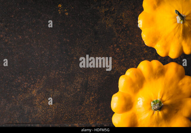 Yellow fresh pattypan squash at the right of the rusty metal background horizontal - Stock Image