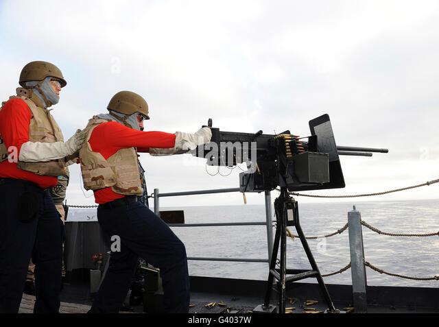 Aviation Ordnanceman fires a .50-caliber machine gun. - Stock Image