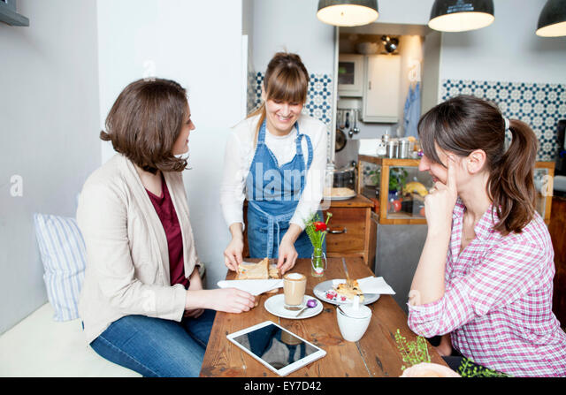 Guests and waitress in coffee shop - Stock Image