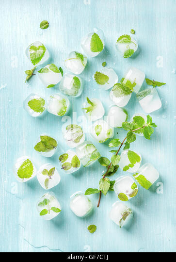 Ice cubes with frozen mint leaves inside on blue Turquoise background, top view - Stock Image