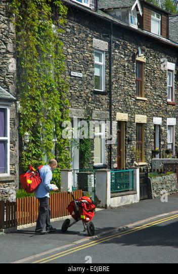 Postman on his round, Cumbria, England UK - Stock Image