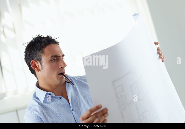 portrait of mid adult architect reading blueprint and smiling - Stock Image