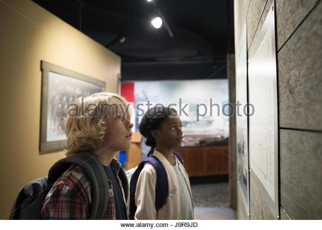 Curious multi-ethnic students looking up at exhibit on field trip in war museum - Stock-Bilder