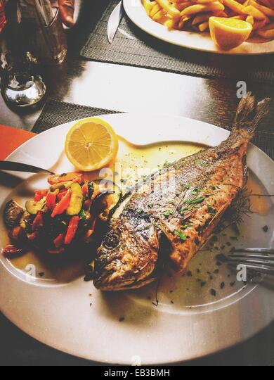 Grilled fish with roasted vegetables - Stock Image