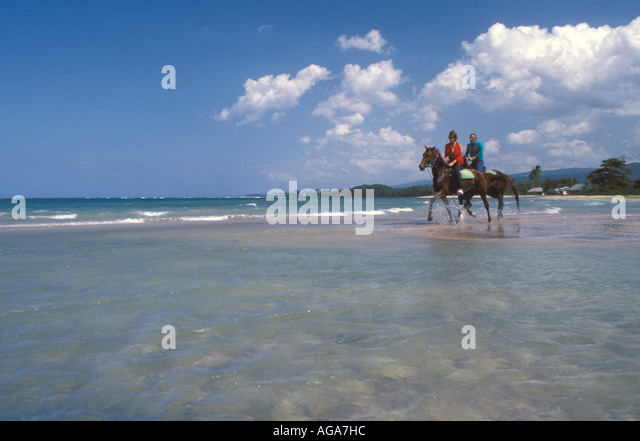 Jamaica Chukka Cove couple horseback riding in the surf - Stock Image