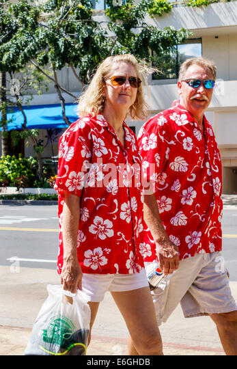Hawaii Hawaiian Honolulu Waikiki Beach resort man woman couple matching shirts floral design red - Stock Image