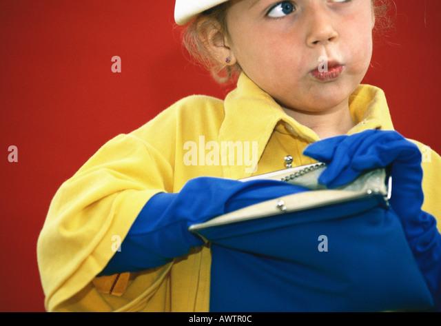 Little girl playing dress-up, reaching inside handbag - Stock Image