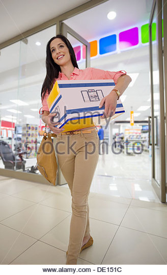 Smiling woman leaving electronics store with boxed speakers - Stock-Bilder
